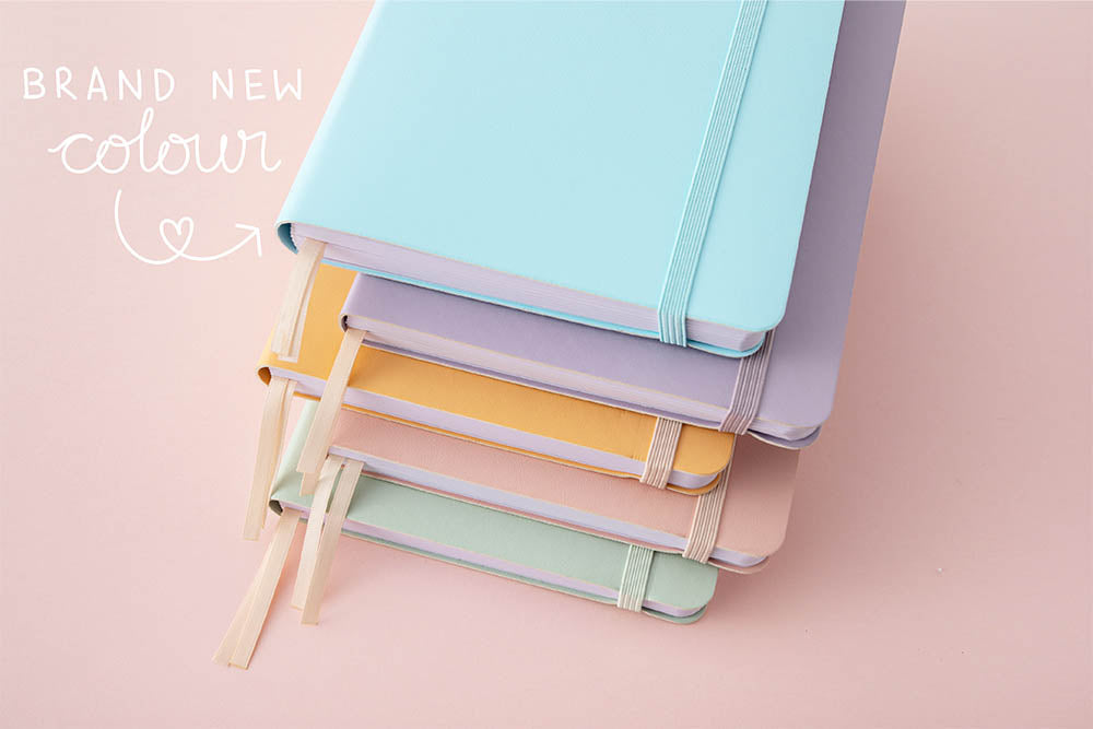Close up of Tsuki Pastel Edition Bullet Journals in mint matcha and pink sakura and honey butter and lilac taro and brand new bluebell colour stacked on light pink background
