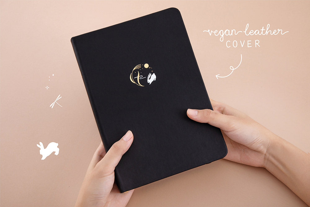 Tsuki 'Moonlit Wish' Limited Edition Bullet Journal with vegan leather cover held in hands in light brown background
