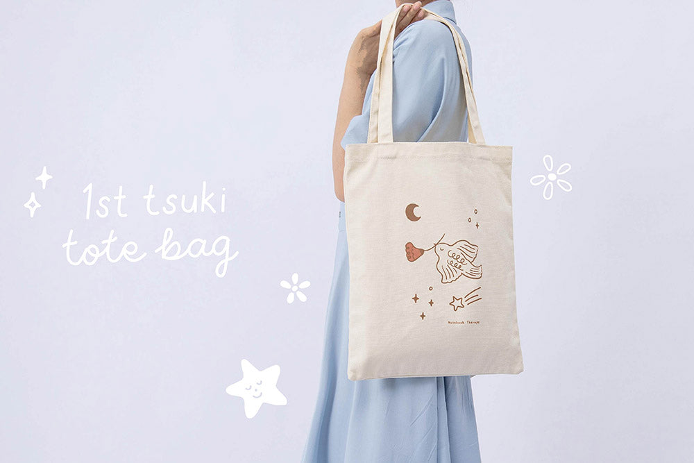 First Tsuki 'Moonflower' Limited Edition Tote Bag shown on model's shoulder in light blue background