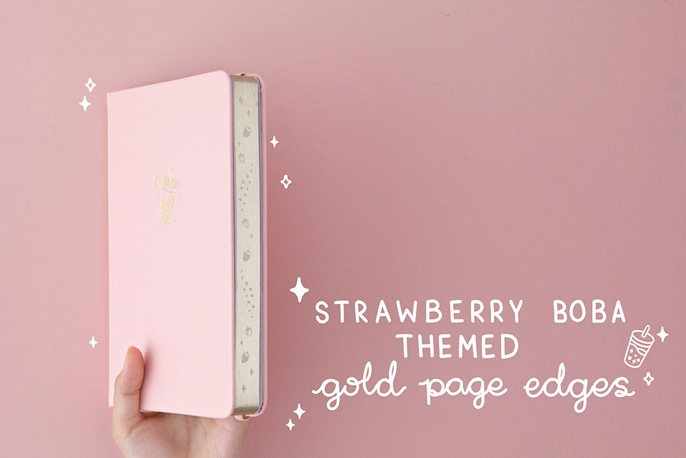 suki 'Ichigo' Limited Edition Boba Bullet Journal with strawberry boba themed gold page edges held in hands at an angle in light pink background