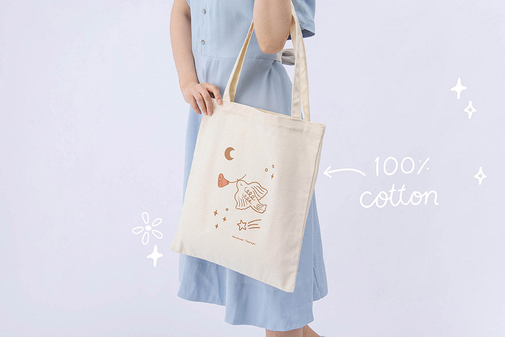 100% cotton Tsuki 'Moonflower' Limited Edition Tote Bag held in model's hands in light blue background