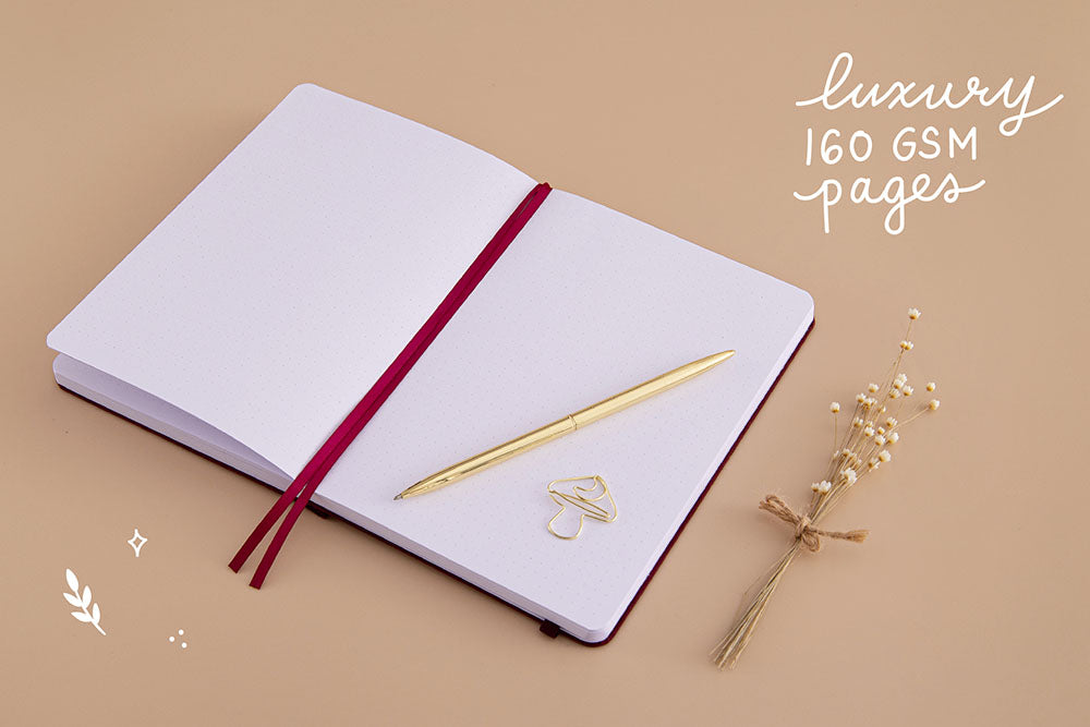 Open page spread of Tsuki 'Kinoko' Limited Edition Bullet Journal with luxury 160GSM pages and free paperclip gift with gold pen and dried flowers on beige background