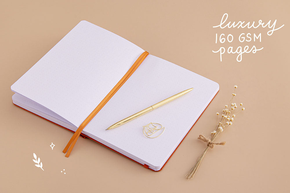 Open page spread of Tsuki 'Kitsune' Limited Edition Fox Bullet Journal with luxury 160GSM pages and free paperclip gift with gold pen and dried flowers on beige background
