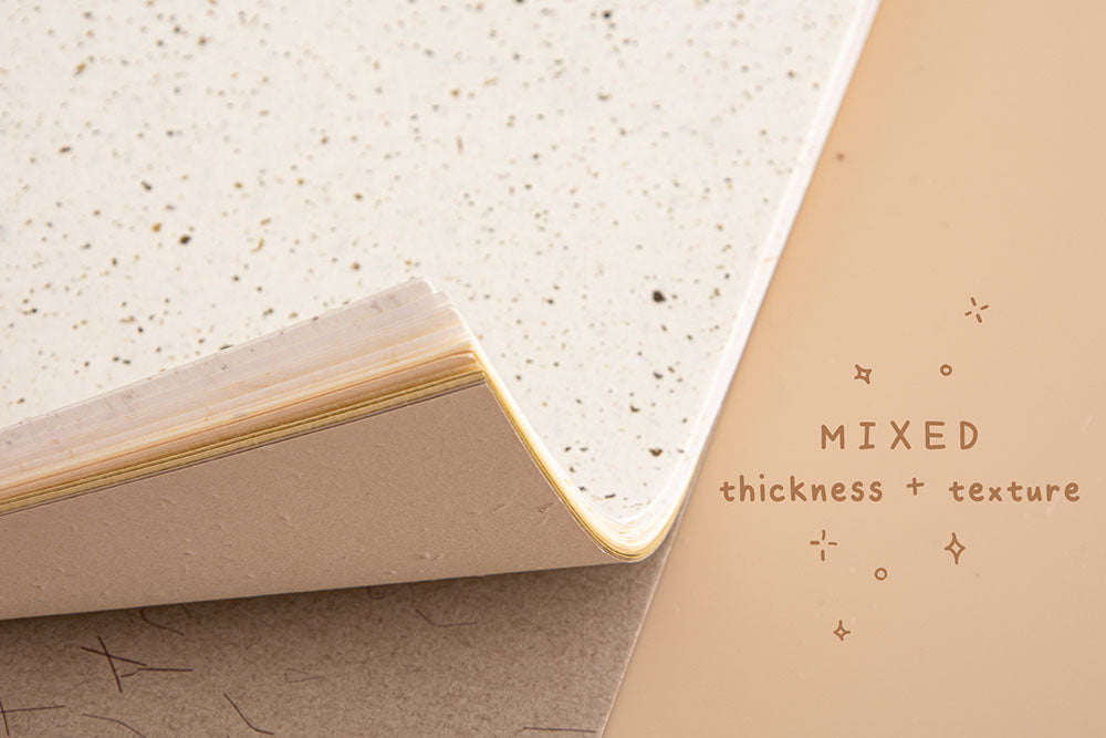 Close up of Tsuki Mixed Scrapbook Paper Pack corners with mixed thickness and texture on beige background