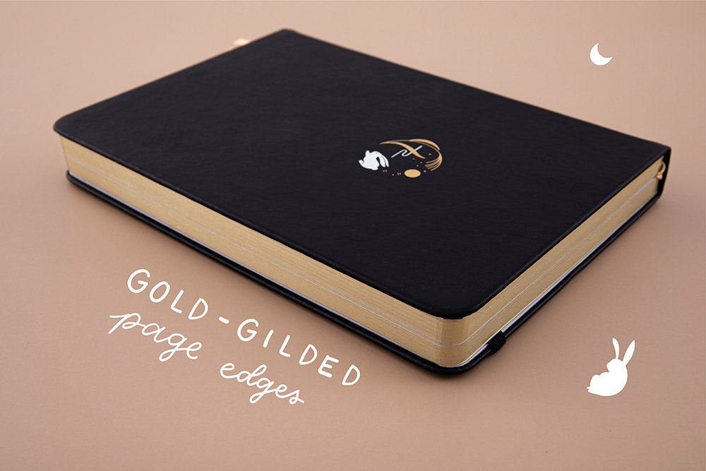 Tsuki 'Moonlit Wish' Limited Edition Bullet Journal with gold gilded page edges on light brown background