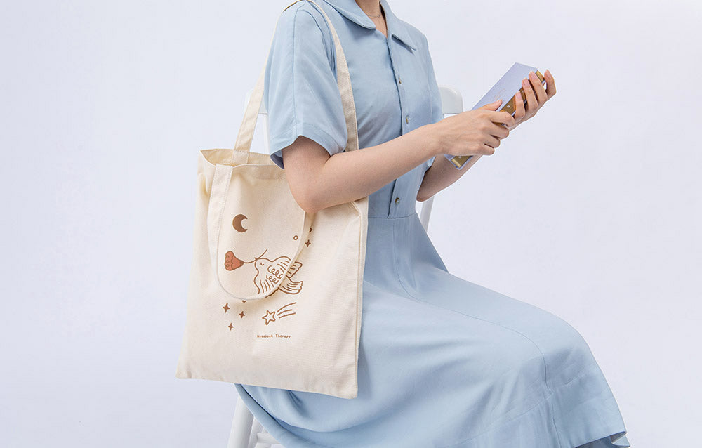 Tsuki 'Moonflower' Limited Edition Tote Bag shown on model's arm with 'Full Bloom' Limited Edition Bullet Journal held in hands in light blue background