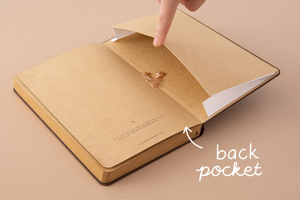 Open back page pocket of Tsuki Kraft Paper Limited Edition Bullet Journal in Nara with free bookmark gift held in hand on beige background