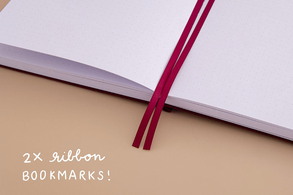 Open page spread of Tsuki 'Kinoko' Limited Edition Bullet Journal with two bookmark ribbons on beige background