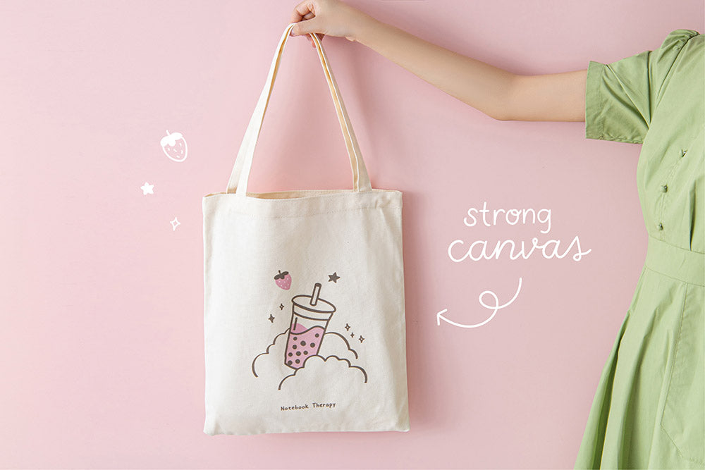 Tsuki 'Ichigo' Boba Tote Bag with strong canvas held in hands in light pink background