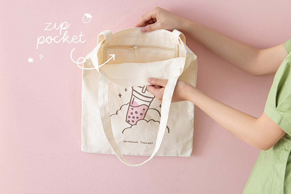 Tsuki 'Ichigo' Boba Tote Bag held in hands with inside zippable pocket in light pink background