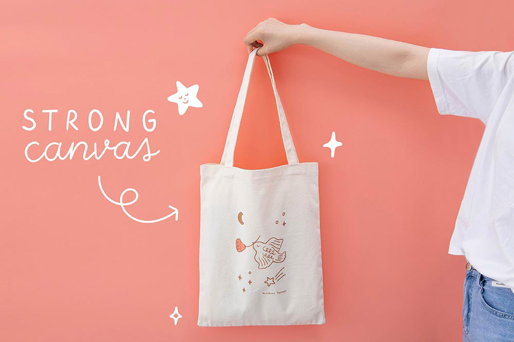 Strong canvas Tsuki 'Moonflower' Limited Edition Tote Bag held held in hands in coral pink background