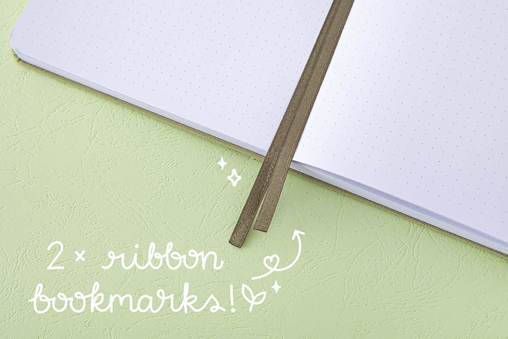 Close up of open pages and two bookmark ribbons of Tsuki 'Matcha Matcha' Limited Edition Bullet Journal on matcha green background
