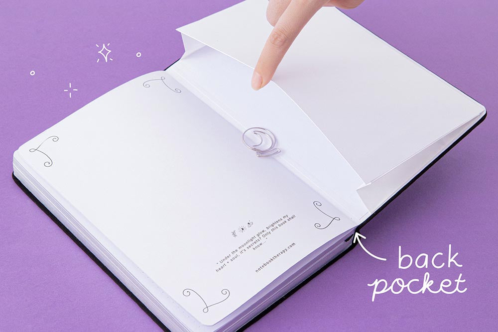 Open back page pocket of Tsuki 'Moonlit Spell' Limited Edition Holographic Bullet Journal held in hand with free bookmark gift on purple background
