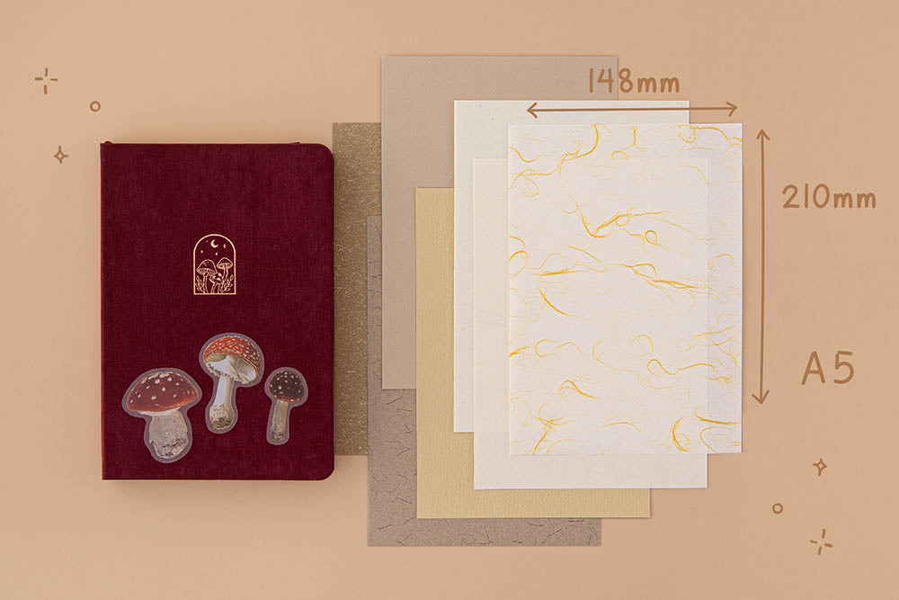 Tsuki Mixed Scrapbook Paper Pack in A5 size with free mushroom stickers and Tsuki 'Kinoko' Limited Edition Bullet Journal on beige background