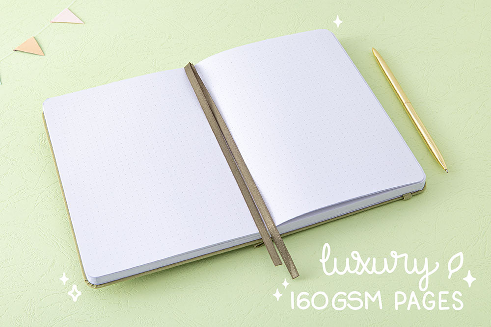 Open pages and two bookmark ribbons of Tsuki 'Matcha Matcha' Limited Edition Bullet Journal with luxury 160GSM pages with gold pen and bunting on matcha green background