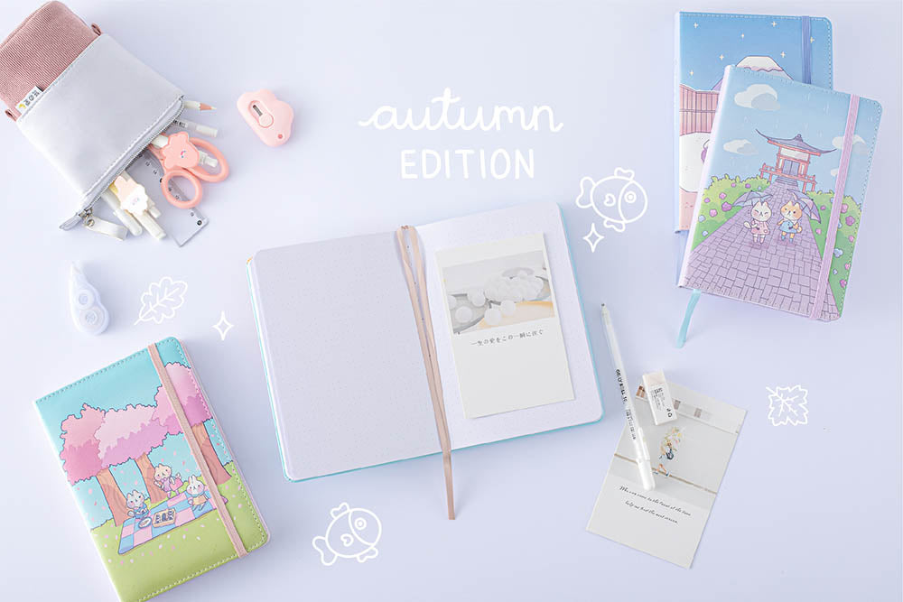 Tsuki 'Four Seasons: Autumn Edition' Bullet Journal made with milkkoyo held in hand with Tsuki 'Four Seasons: Summer Edition' notebook and Tsuki 'Four Seasons: Spring Edition' bujo and Tsuki 'Four Seasons: Winter Edition' bullet journal with Tsuki Pop-Up Pencil case and assorted stationery supplies on lilac background