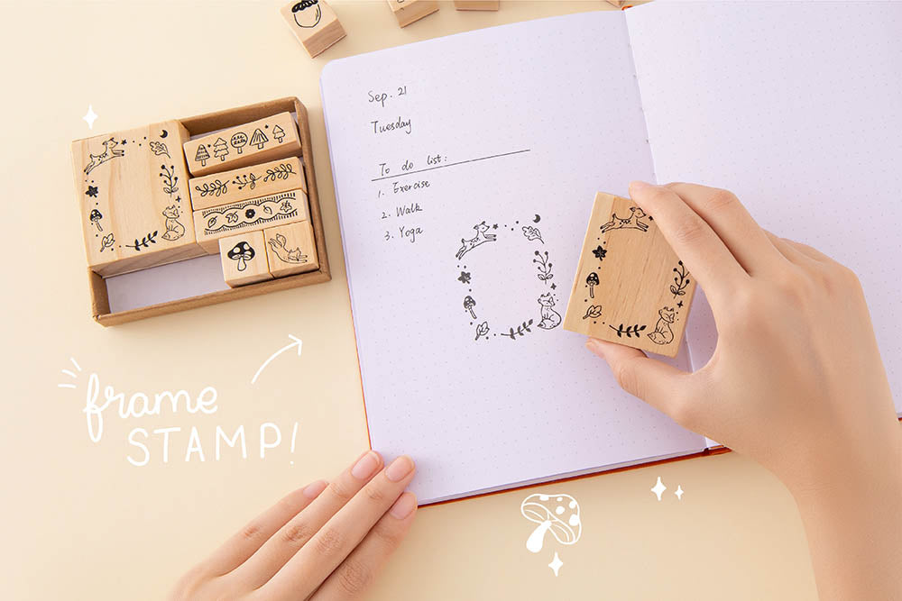 Tsuki 'Maple Dreams' Bullet Journal Stamp Set with frame stamp held over open bullet journal page spread in hands on cream background