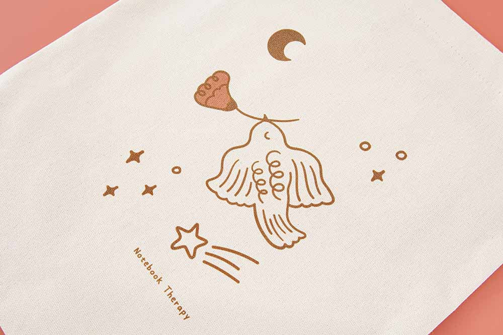 Close up of Suzume bird art design of Tsuki 'Moonflower' Limited Edition Tote Bag on coral pink background