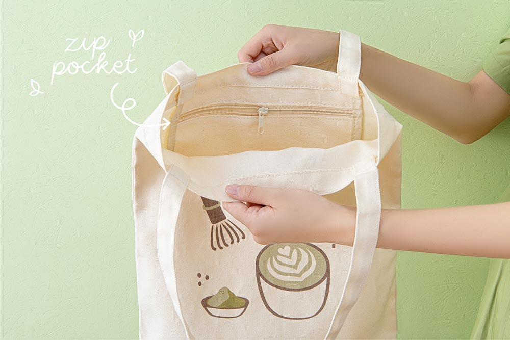 Close up of the inside of Tsuki 'Matcha Matcha' Tote Bag held in hands with inside zippable pocket in matcha green background