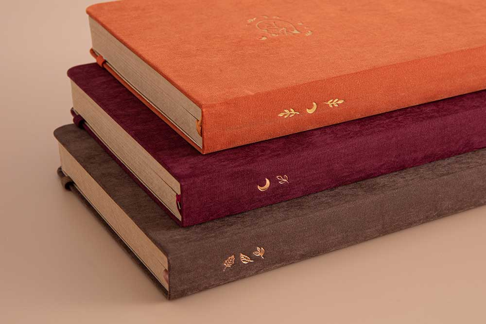 Close up of Tsuki Kraft Paper Limited Edition Bullet Journals in Nara and Kitsune and Kinoko stacked together in beige background