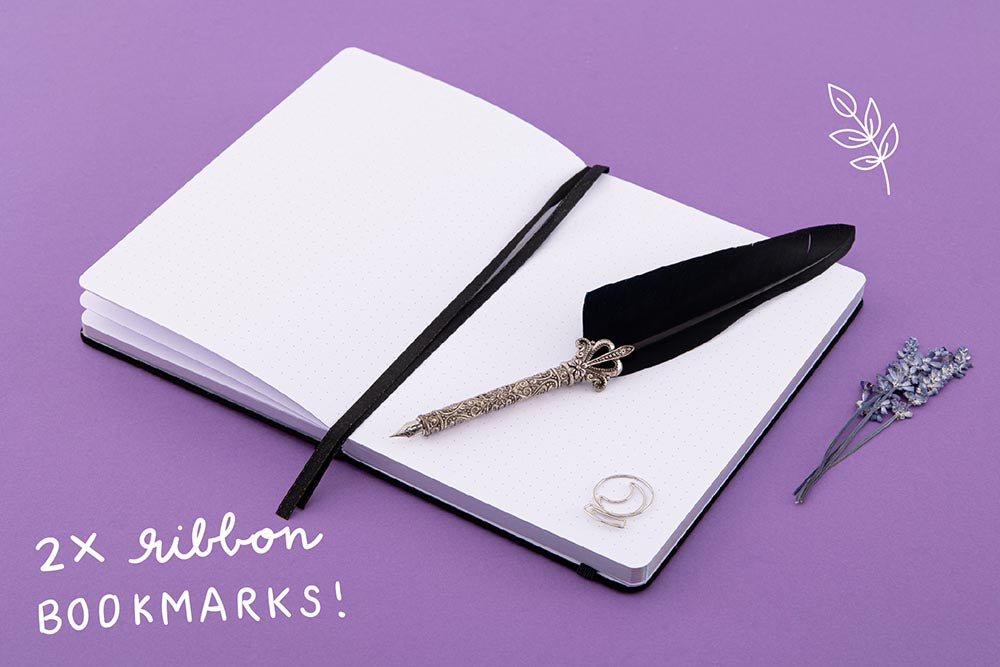 Open page spread of Tsuki 'Moonlit Spell' Limited Edition Holographic Bullet Journal with two bookmark ribbons and free bookmark gift with black feather quill and lavender sprigs on purple background