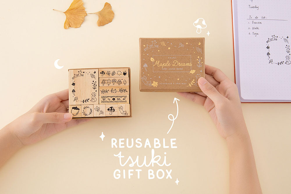Tsuki 'Maple Dreams' Bullet Journal Stamp Set with reusable tsuki gift box held in hands with autumn leaves and Tsuki 'Kitsune' Limited Edition Fox Bullet Journal in cream background