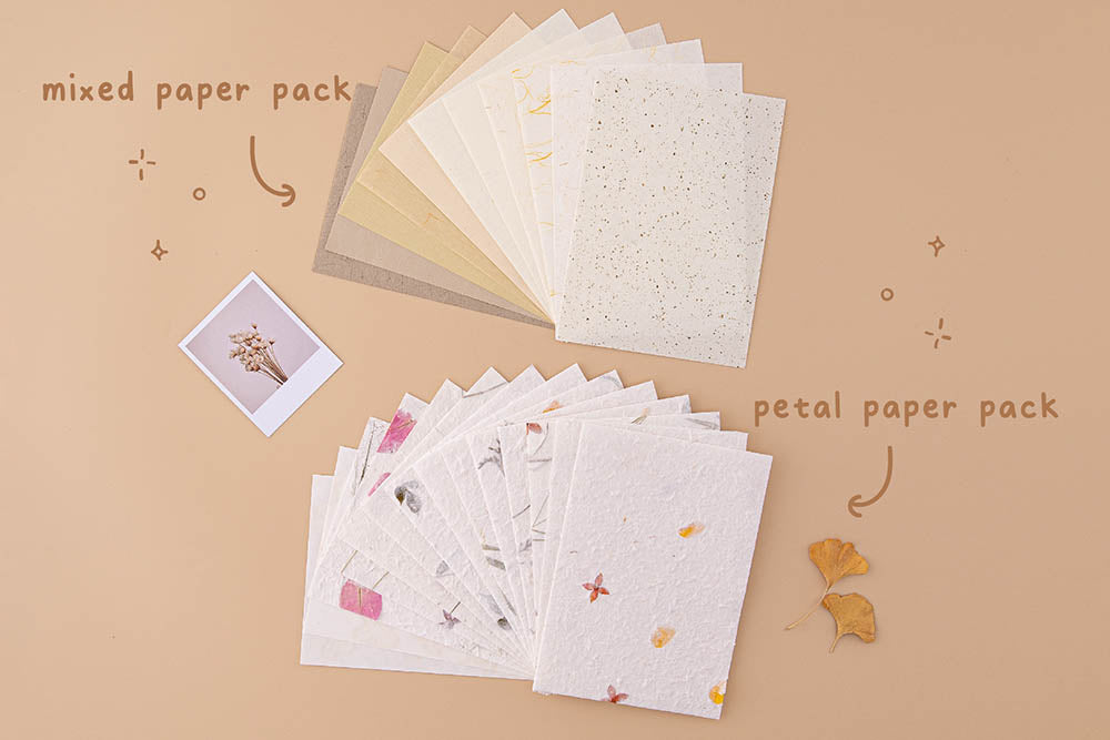 Tsuki Mixed Scrapbook Paper Pack with Tsuki Handmade Petal Paper Pack fanned out with polaroid picture and autumn leaves on beige background