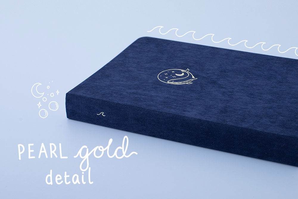 Tsuki deep blue soft velvet Gentle Giant luxury edition notebook at an angle with pearl gold detail on cover and spine on blue background