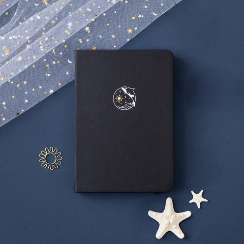 Tsuki deep black Playful Orca limited edition notebook at an angle with starfish and free sunshine gift on dark blue background