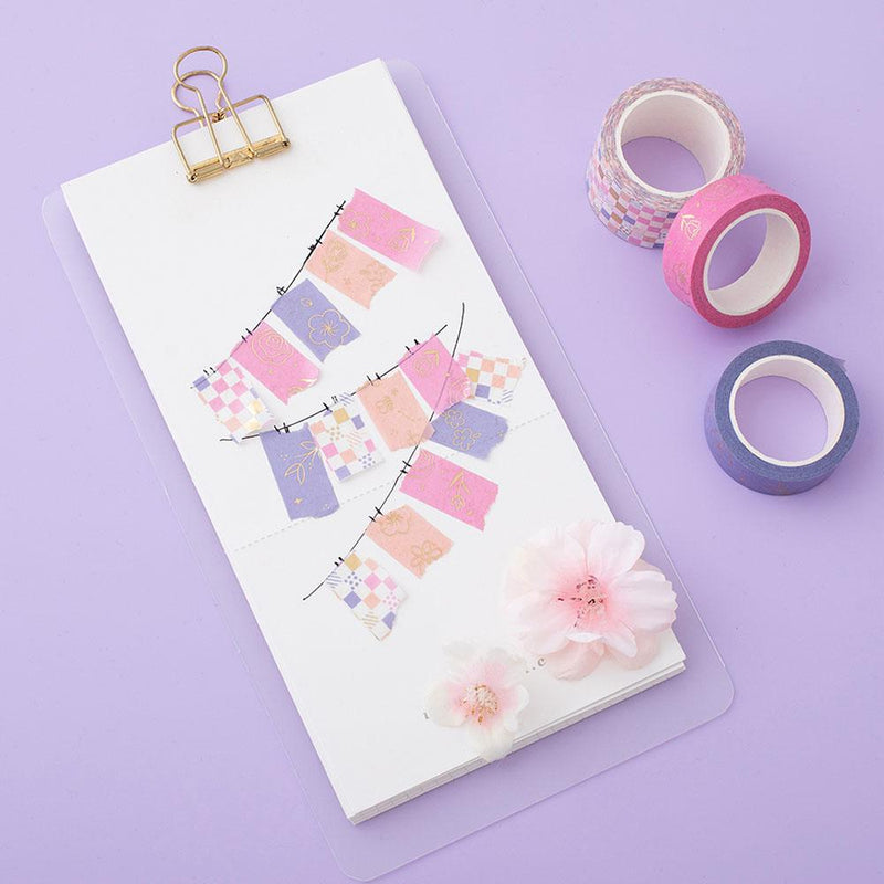 Tsuki Floral washi tapes laid out with mini banners made with washi tape on card, on lilac background