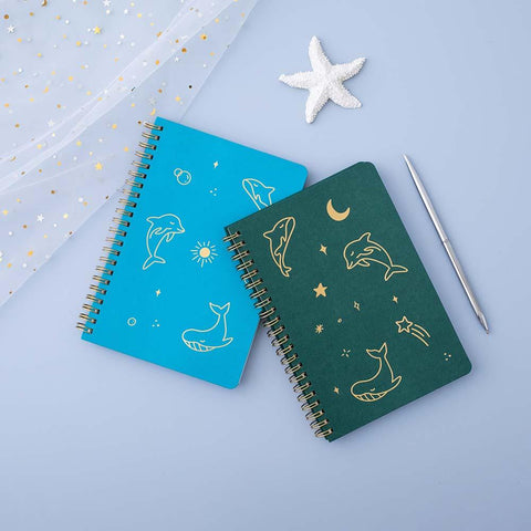 Tsuki Ocean Edition Ring Bound notebooks in aqua blue and deep teal with silver pen and starfish on blue background