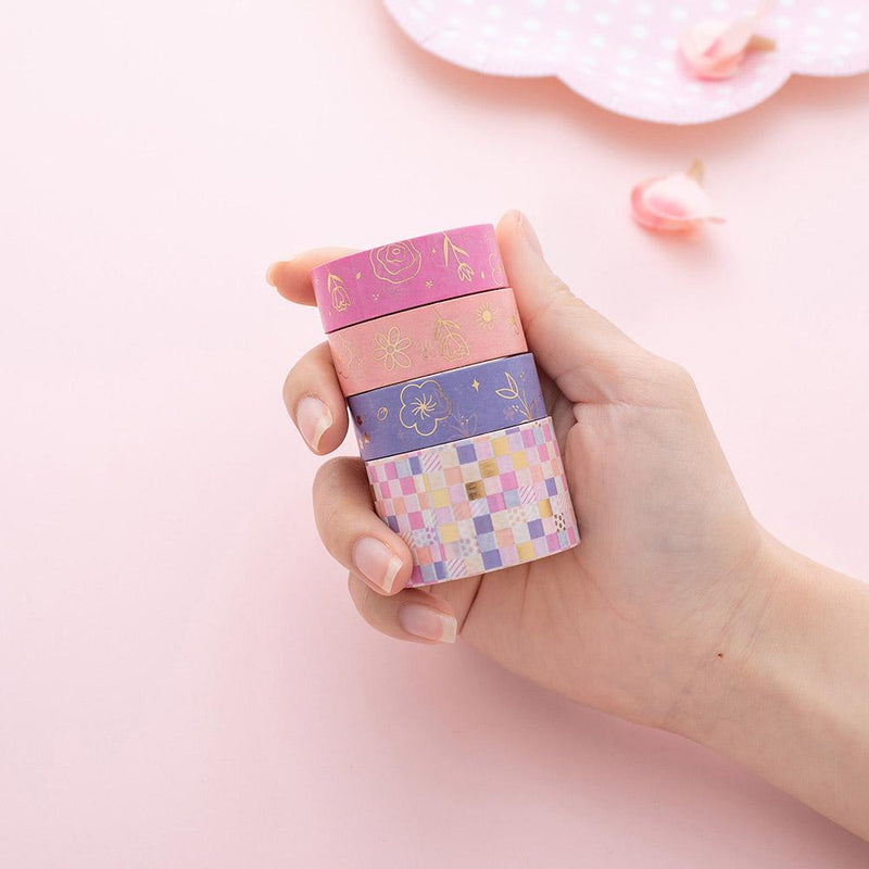 Stacked Tsuki Floral washi tapes held in hand on pink background