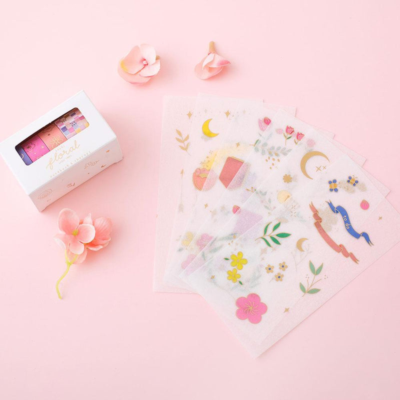 Tsuki Floral collection washi tapes in boxed packaging and 6 sticker sheet laid out on flower ornament and pink background
