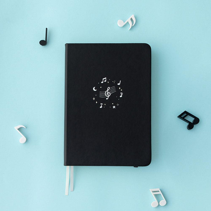 Tsuki Lunar Notes bullet journal with music notes flat lay image on blue background