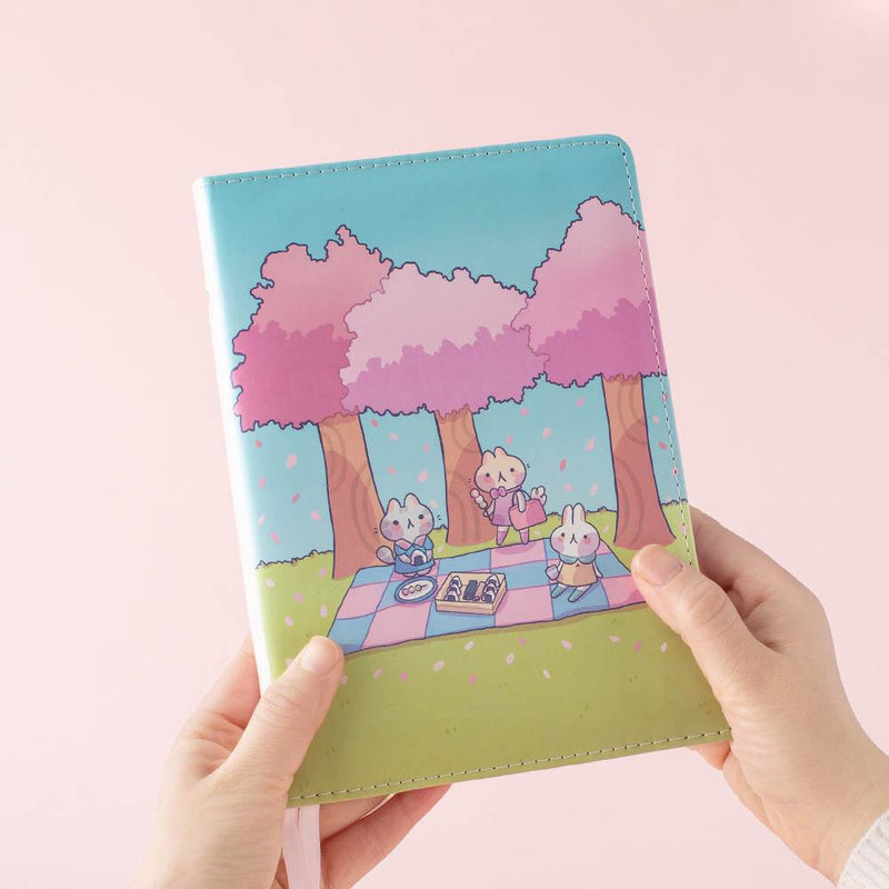 hand holding spring edition bullet journal in pink background