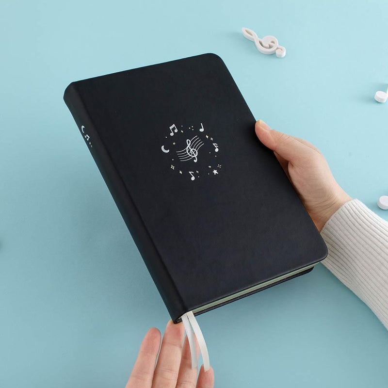 Tsuki Lunar Notes bullet journal in hands image in blue background