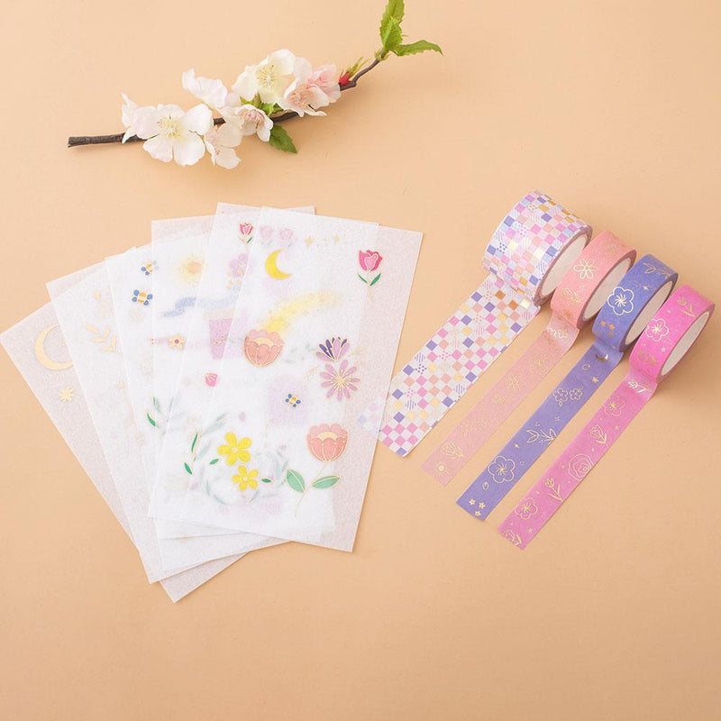 Tsuki Floral collection washi tapes + sticker sheets layout out on the peach background