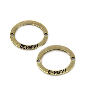 "Conector ovalado en tono dorado ""BE HAPPY"" 19x23mm Conector de Bead Gallery"