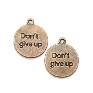 "Charm de lentejas de 21 mm en tono cobre ""Don't give up"" - 2 piezas de Halcraft Collection"