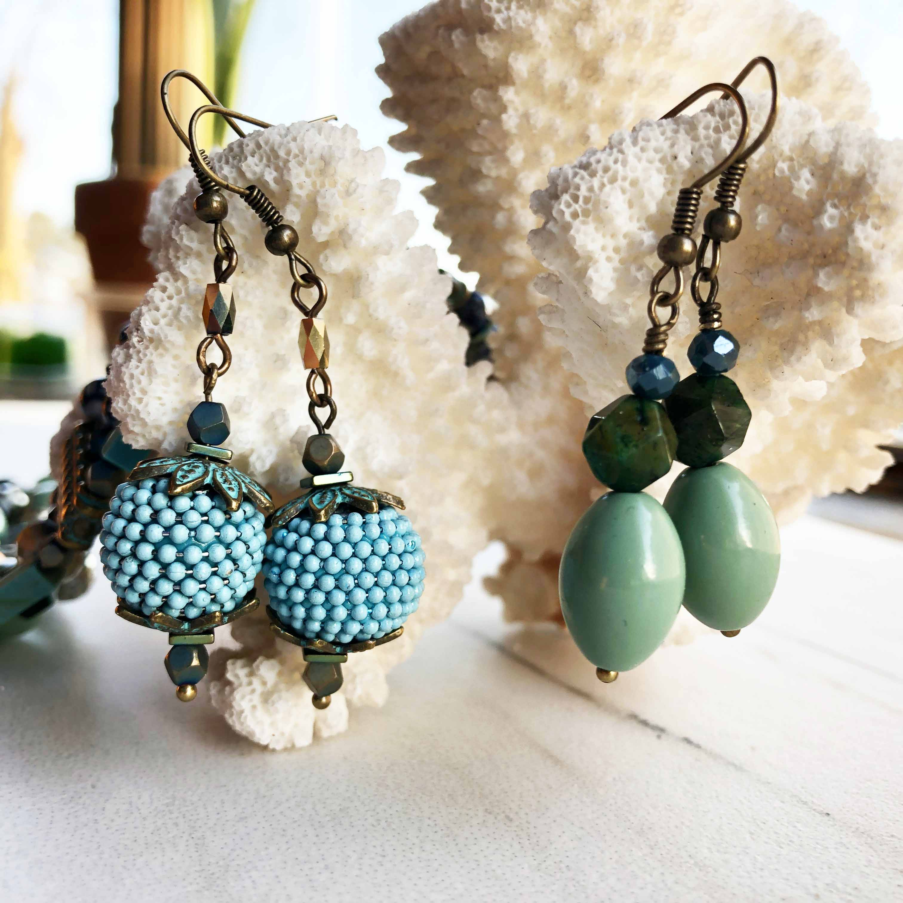 Blue and turquoise beaded earrings hanging on coral