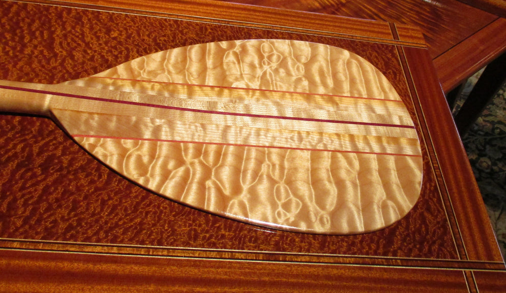 Quilted Maple Canoe Paddle on a Sapele table