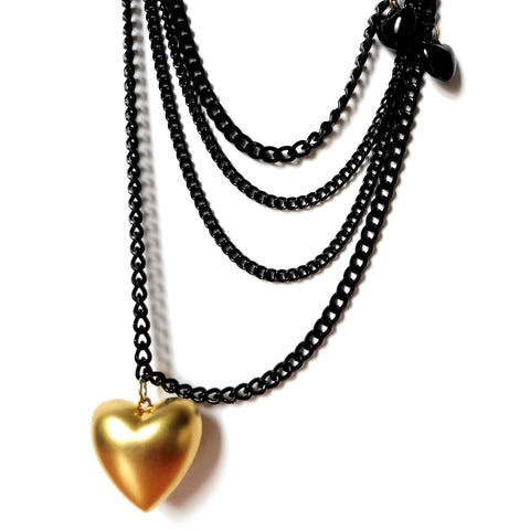Light weight black quin chain necklace made with almanite with large matte-finish gold heart and two baby-fat black heart charms. Close-up image. ync by nny. Yn Couture by Nana N Yoshida.