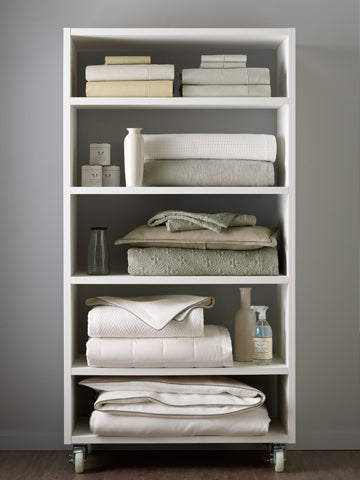 A linen cabinet on wheels filled with various sheets, blankets, and related items