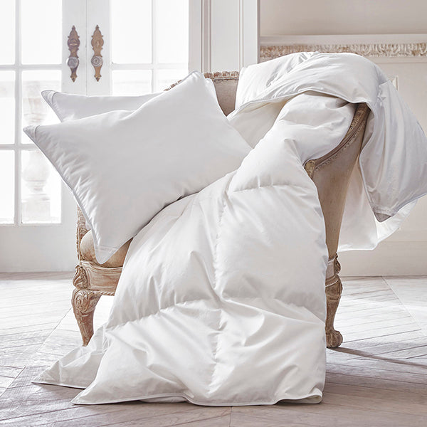white down pillows and duvet comforter on chair