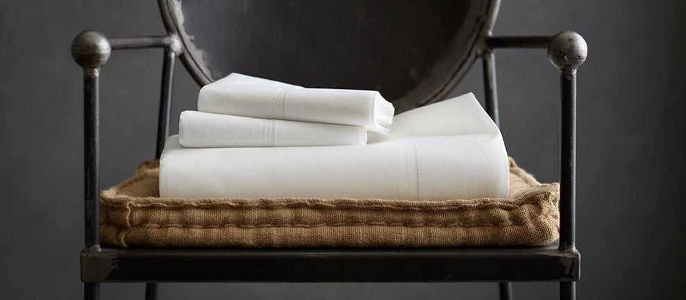 white sheets folded in a basket