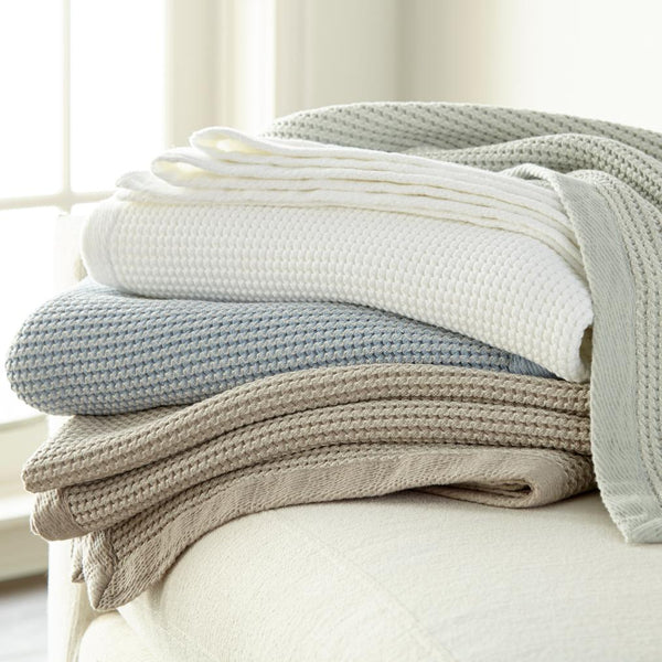 messy stack of Hudson blankets in various muted colors