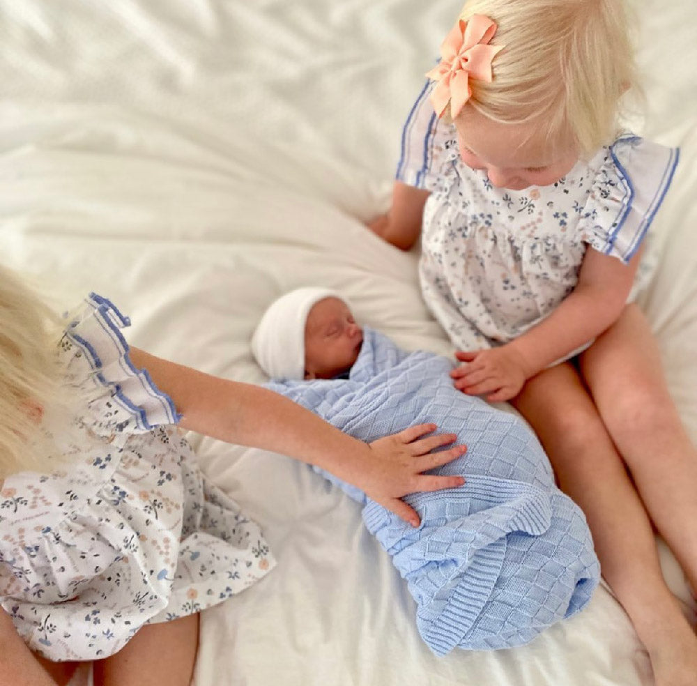 Little girls with baby boy swaddles with Naptime Knitted Baby Blanket