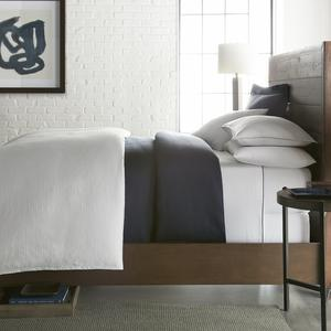 grey duvet cover and navy coverlet styled on bed with matching shams