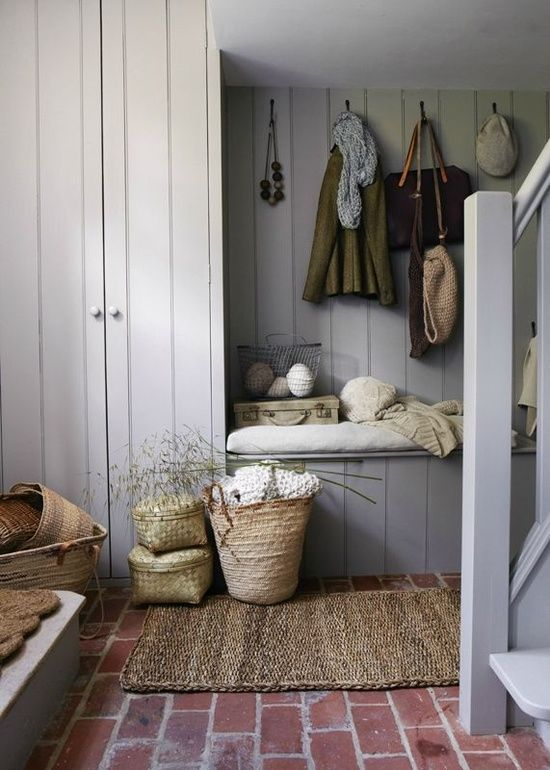 Mudroom in gray with brick flooring and woven baskets and accent pieces