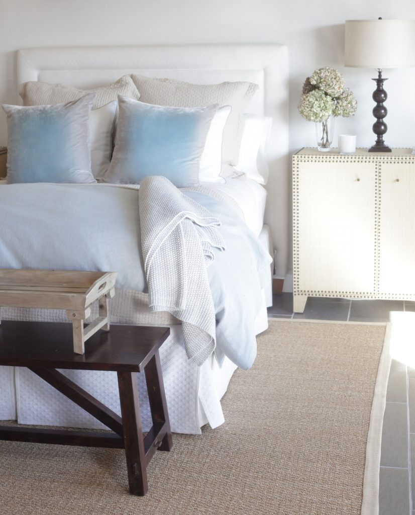 Bedding design by Brooke & Steve Giannetti, bed in pastel shades next to a night stand with white flowers
